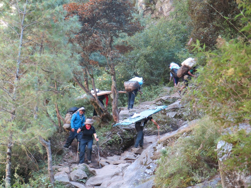 Porters carrying building materials up the trail