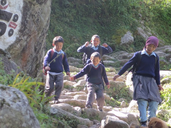Children running home from school EBC trek trail Nepal
